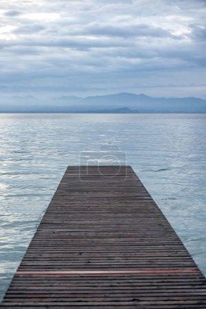 Empty footbridge on lake at dusk