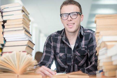 Photo pour Jeune homme étudiant à la bibliothèque du collège, concept d'éducation - image libre de droit