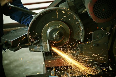 Photo for Industrial worker cutting and welding metal with many sharp sparks - Royalty Free Image