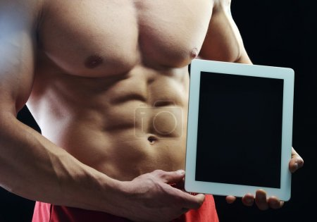 Body builder champion posing in studio with tablet