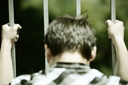 Man in jail holding grates