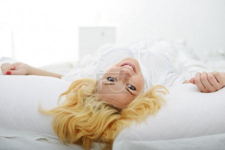 Female on bed in bedroom waking up