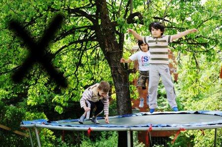 Photo for Happy children enjoying childhood on trampoline - Royalty Free Image