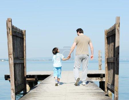 Photo pour Père et fils sur le quai près d'un beau lac - image libre de droit