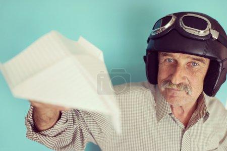 Photo pour Homme drôle senior en tant que pilote avec chapeau et lunettes en utilisant un avion en papier - image libre de droit