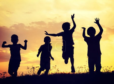 Photo for Group of happy children playing on meadow on sunset - Royalty Free Image
