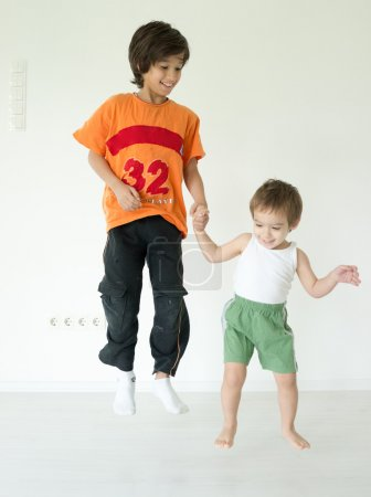 Adorable little boys at home jumping
