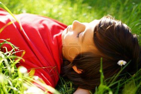 Photo pour Petit garçon profitant de l'heure d'été allongé sur l'herbe verte prairie - image libre de droit
