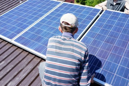 Man installing alternative energy photovoltaic solar panels