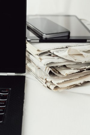 Modern gadgets and newspapers