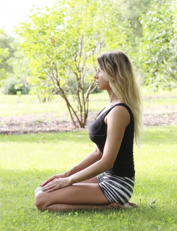 Beautiful woman practicing outdoor yoga