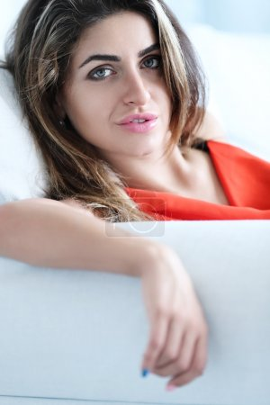 Lovely woman sits in white sofa