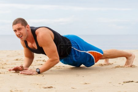 Man doing push-up on the beach