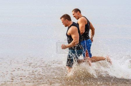 Guys running on the beach