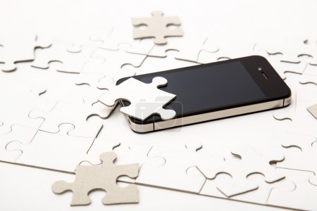 White puzzle with mobile phone