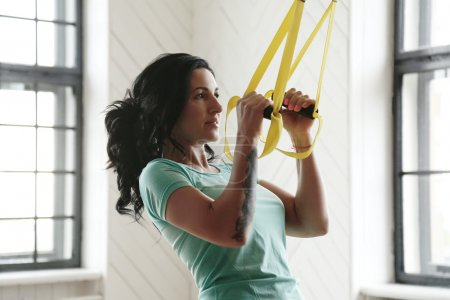 Beautiful woman training trx