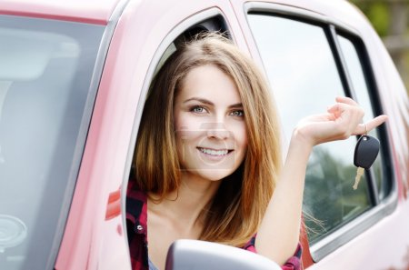 Photo for Young happy woman with car key out of window - Royalty Free Image