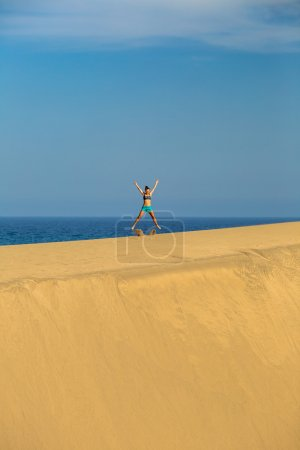 Woman with arms up outstretched jumping on sand desert dunes