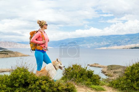 Photo for Woman hiking with akita inu dog on seaside trail. Recreation and healthy lifestyle outdoors in summer mountains and sea nature. Beautiful inspirational landscape. Trekking and activity concept. - Royalty Free Image