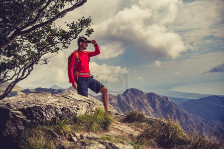 Photo for Hiking man, climber or trail runner looking at inspirational mountains landscape view. Fitness and healthy lifestyle outdoors in summer nature. Accomplished climber or traveller. - Royalty Free Image