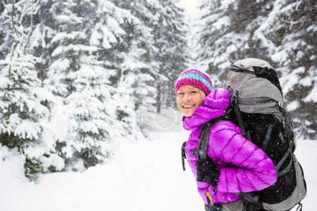 Photo for Happy young woman hiking in white winter forest woods with backpack. Girl walking on snowy trail. Inspirational Travel and healthy lifestyle Motivation and. Camping outdoors in winter landscape. - Royalty Free Image