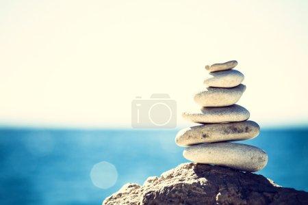 Photo pour Équilibre de pierres, vintage retro instagram comme hiérarchie pile sur fond de mer bleue. Concept de spa ou de bien-être, de liberté et de stabilité sur les rochers. - image libre de droit