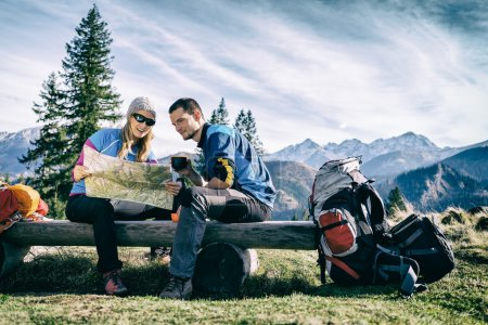 Photo pour Man and woman hikers hiking in mountains. Young couple camping, looking at map and planning trip or get lost. Getting rest and drinking coffee or tea - image libre de droit