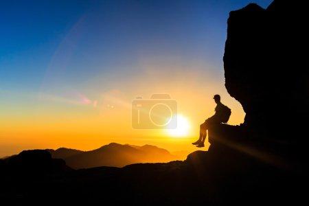 Photo pour Silhouette homme randonnée en montagne, coucher de soleil et océan. Randonneur masculin avec sac à dos au sommet de la montagne regardant belle vue sur le paysage nocturne et le ciel bleu, concept de liberté - image libre de droit
