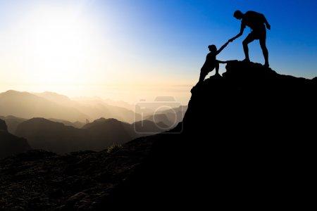 Photo pour Travail d'équipe couple randonnée s'entraider confiance assistance silhouette dans les montagnes, coucher de soleil. Équipe d'alpinistes homme et femme randonneur s'entraidant au sommet de la montagne, confiance en l'escalade, beau paysage de coucher de soleil . - image libre de droit