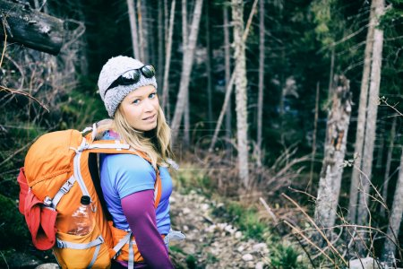Woman hiking in winter cold dark winter forest