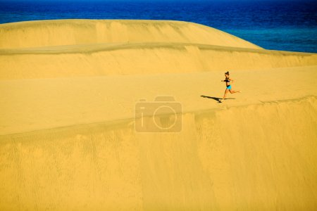 Woman running happy on beach and dunes