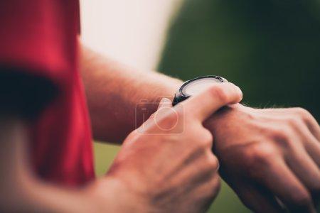 Photo pour Coureur utilisant la course de formation de moniteur de fréquence cardiaque, smartwatch vérifiant la performance ou Gps. Athlète de l'homme regardant le chronomètre. Plan rapproché sain de coureur sur l'entraînement de course de sentier. Technologie portable pour le suivi des activités. - image libre de droit