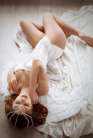 Photo for Sexy beautiful brunette girl in underclothes lying on a white sheet - Royalty Free Image