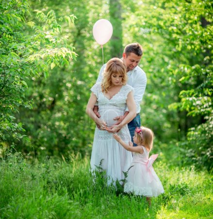Pregnant woman with her husband and daughter in garden