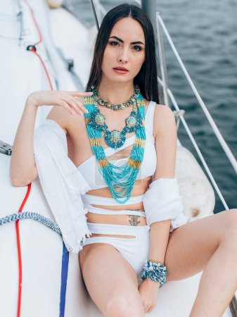 Woman in stylish swimsuit on yacht