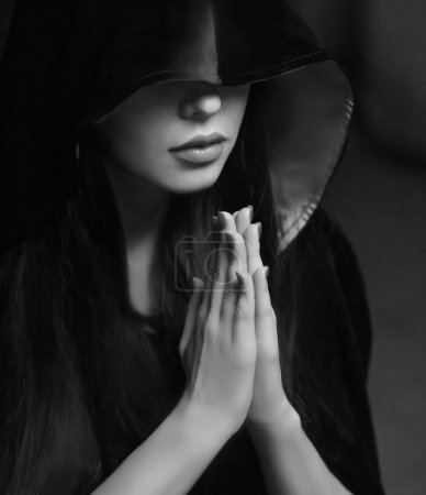 Beautiful woman with black cloak over black backgr...