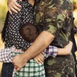 Wife and son hugging soldier