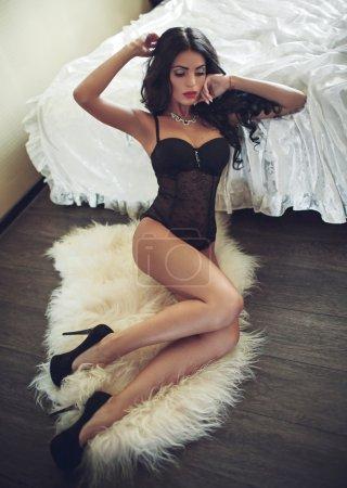 Photo pour Belle jeune fille brune sexy en sous-vêtements noirs assise sur la fourrure - image libre de droit