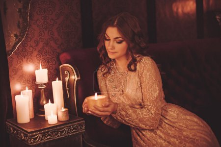 Portrait of beautiful young woman with candles...