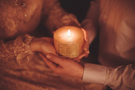 Photo for Candle burning in hands in the dark - Royalty Free Image