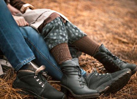 Photo pour Fermer jambes de couple assis sur la pelouse du parc - image libre de droit