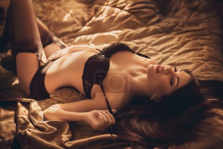 girl in black underclothes lying on the bed
