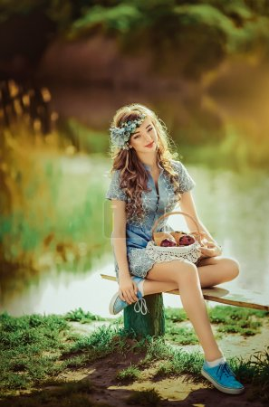 young woman sitting near pond