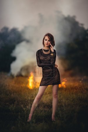 girl stands on a background of burning fire