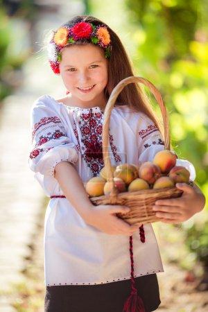 Photo pour Petite fille ukrainienne dans jardin d'été avec panier de pêches mûres - image libre de droit