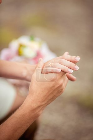 Groom holds his bride's hand