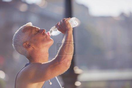 senior jogging man drinking fresh water from bottle