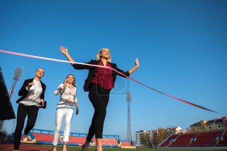 Business women running on racing track