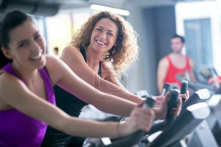 Women working out at fitness cycle