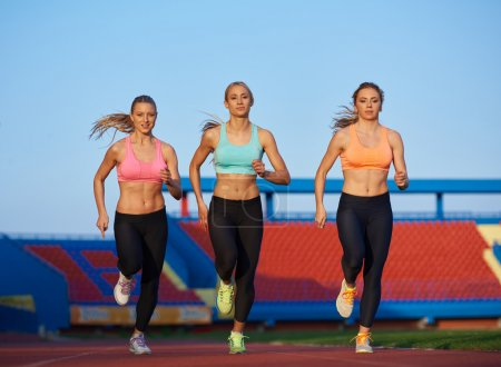 Athletic women group  running on athletics race track